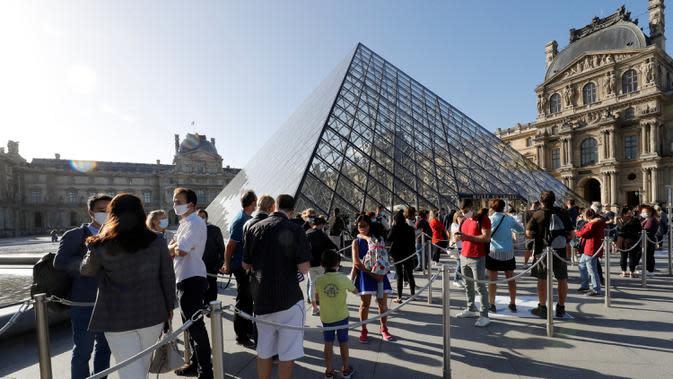 Museum Louvre Kembali Dibuka: Pengunjung mengantre di piramida Louvre, pintu masuk ke Museum Louvre pada hari pertama pembukaan di Paris (6/7/2020). Setelah berbulan-bulan ditutup akibat lockdown Covid-19, Museum Louvre kembali dibuka pada 6 Juli 2020. (AFP/Francois Guillot)