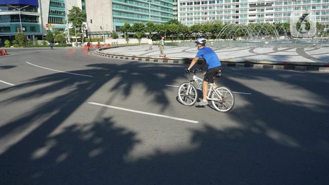 Pesepeda melintas di kawasan Bundaran HI, Jakarta, Minggu (24/5/2020). Adanya PSBB serta Hari Raya Idul Fitri 1441 H dimanfaatkan sebagian warga untuk bersepeda di jalan protokol yang sepi dibanding hari biasa. (Liputan6.com/Immanuel Antonius)