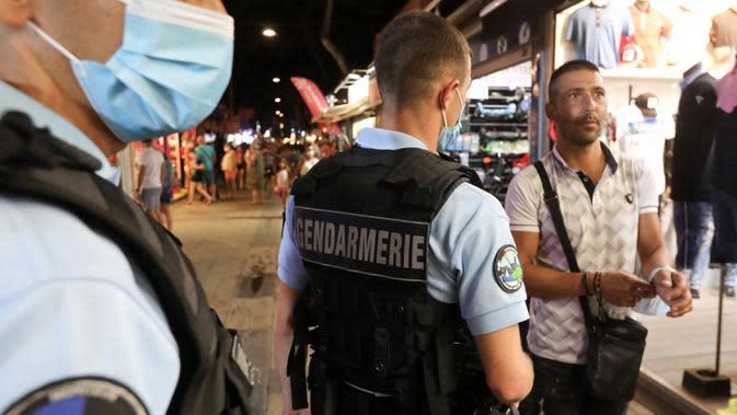 Polisi Prancis berpatroli untuk mengontrol kewajiban penggunaan masker di jalan-jalan Argeles-sur-Mer, Prancis selatan, Rabu (13/8/2020). Pemakaian masker di beberapa area ramai di sekitar Paris merupakan kewajiban sebagai upaya untuk membendung peningkatan tajam infeksi covid-19. (RAYMOND ROIG/AFP)