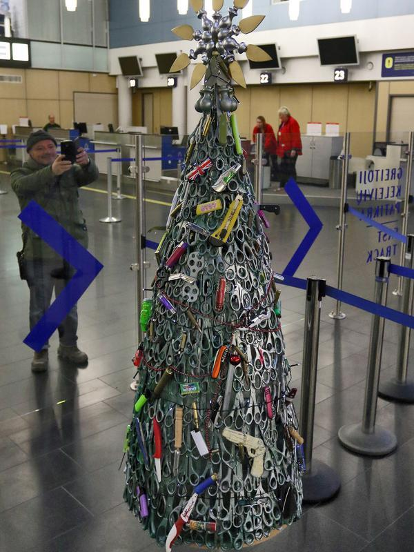 Seorang pria mengambil gambar Pohon Natal yang dirakit dari barang-barang sitaan di Bandara Vilnius, Lithuania pada 12 Desember 2019. Pohon Natal unik ini sekaligus untuk memperingatkan penumpang agar jangan membawa benda-benda terlarang. (Photo by Petras Malukas / AFP)