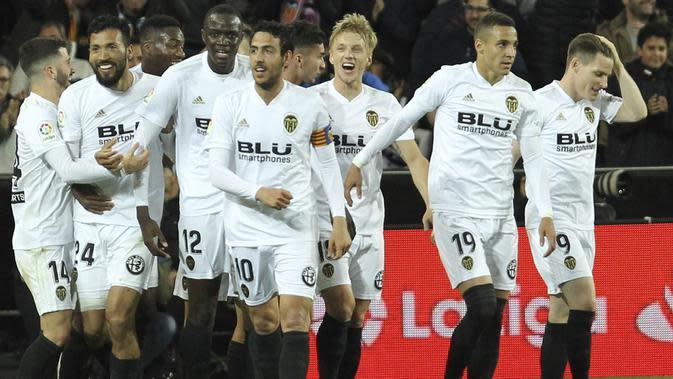 Para pemain Valencia merayakan gol yang dicetak oleh Ezequiel Garay ke gawang Real Madrid pada laga La Liga 2019 di Stadion Mestalla, Rabu (3/4). Valencia menang 2-1 atas Real Madrid. (AP/Alberto Saiz)