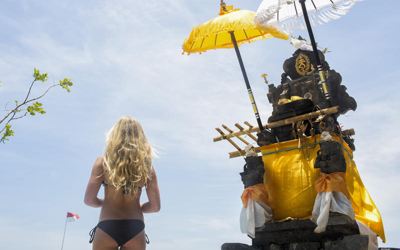 A young tourist in a bikini looks out to sea at a temple at Padang Padang beach in Bali, Indonesia.