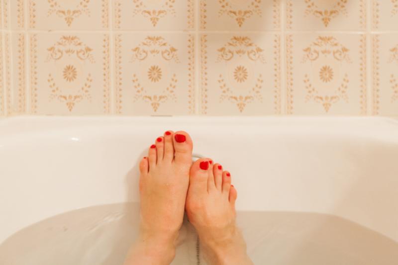 Young female feet in bathtub