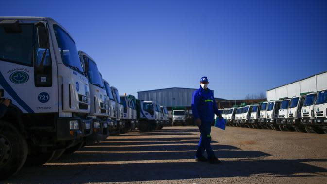 Yamil Peralta berjalan di antara truk-truk sampah di sebuah perusahaan pembuangan limbah di Pilar, pinggiran Buenos Aires, 28 Juli 2020. Di tengah lockdown COVID-19, petinju Olimpiade dan profesional ini mendapat pekerjaan di perusahaan sampah untuk memenuhi kebutuhannya. (AP Photo/Marcos Brindicci)