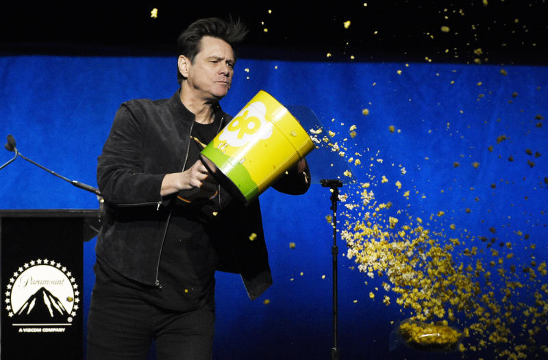 """Jim Carrey, a cast member in the upcoming film """"Sonic the Hedgehog,"""" dumps out a tub of popcorn during the Paramount Pictures presentation at CinemaCon 2019, the official convention of the National Association of Theatre Owners (NATO) at Caesars Palace, Thursday, April 4, 2019, in Las Vegas. (Photo by Chris Pizzello/Invision/AP)"""