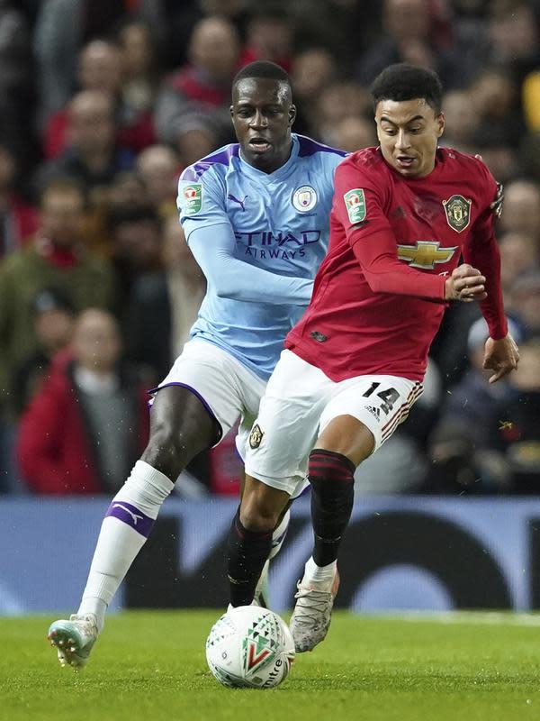 Penyerang Manchester United, Jesse Lingard membawa bola dari kejaran Bek Manchester City, Benjamin Mendy pada pertandingan leg pertama semifinal Piala Liga Inggris di Old Trafford (7/1/2020). City menang 3-1 atas MU. (AP Photo / Jon Super)