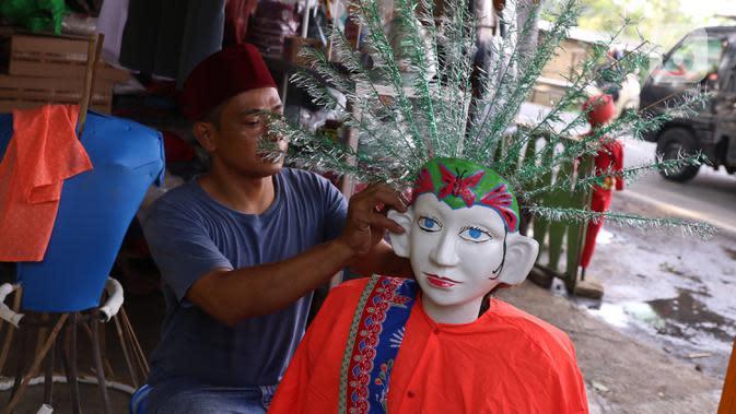Perajin menyelesaikan pembuatan ondel-ondel untuk dijual di Tangerang, Banten, Selasa (14/7/2020). Kementerian Koperasi dan UKM menargetkan digitalisasi 10 juta UMKM pada 2020 menyusul perubahan tren dan perilaku konsumen di tengah pandemi COVID-19. (Liputan6.com/Angga Yuniar)