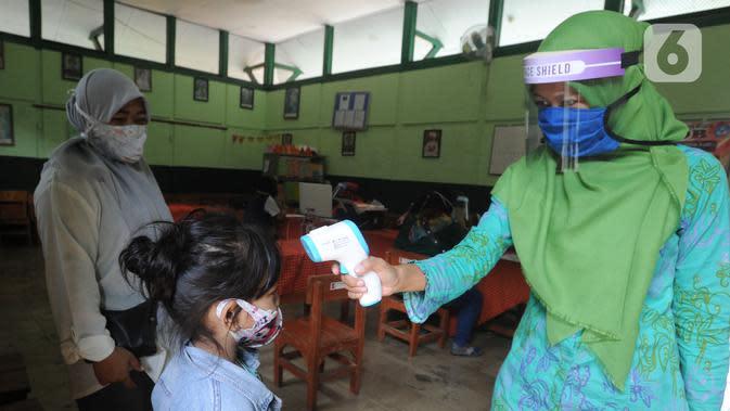 Guru memeriksa seorang siswa saat PPDB tahun ajaran 2020/2021di SDN Pengadilan I Bogor, Jawa Barat, Selasa (9/6/2020). Dinas Pendidikan Kota Bogor membuka waktu pendaftaran PPDB tingkat SD pada 8-11 Juni 2020. (merdeka.com/Arie Basuki)