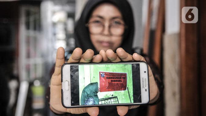 Wiwiek (56) menunjukkan foto saat proyek pembangunan gedung sekolah Pergunas I disegel di Jalan Cempaka Baru I, RT 015/003, Kemayoran, Jakarta, Senin (31/8/2020). Pembangunan itu menutup akses jalur keluar masuk dan harus melewati pintu samping. (merdeka.com/Iqbal S Nugroho)