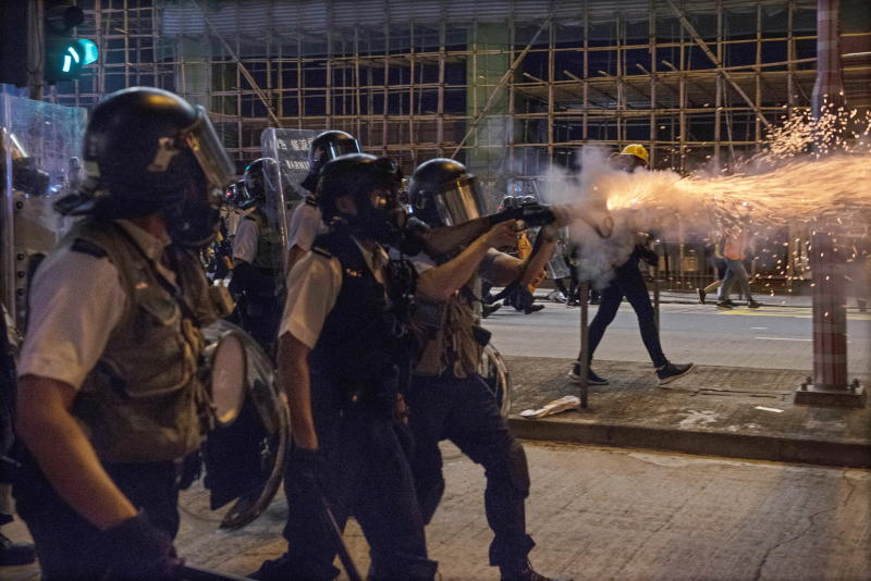 Hong Kong police officers wear protective masks and fire tear gas at protesters in Sham Shui Po.