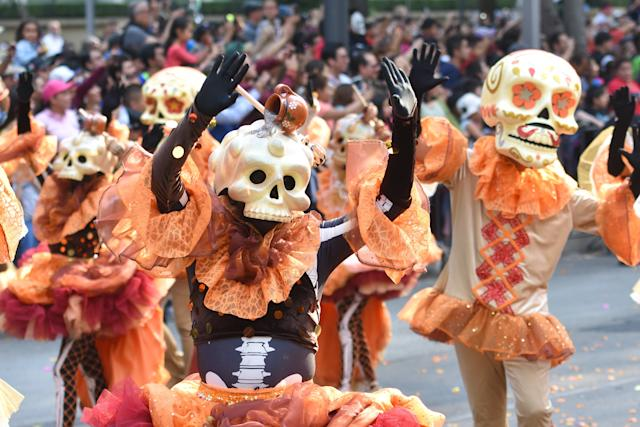People are seen participating in a Skulls Parade as part of Day of the Dead celebrations in Mexico City on Saturday. (NurPhoto via Getty Images)