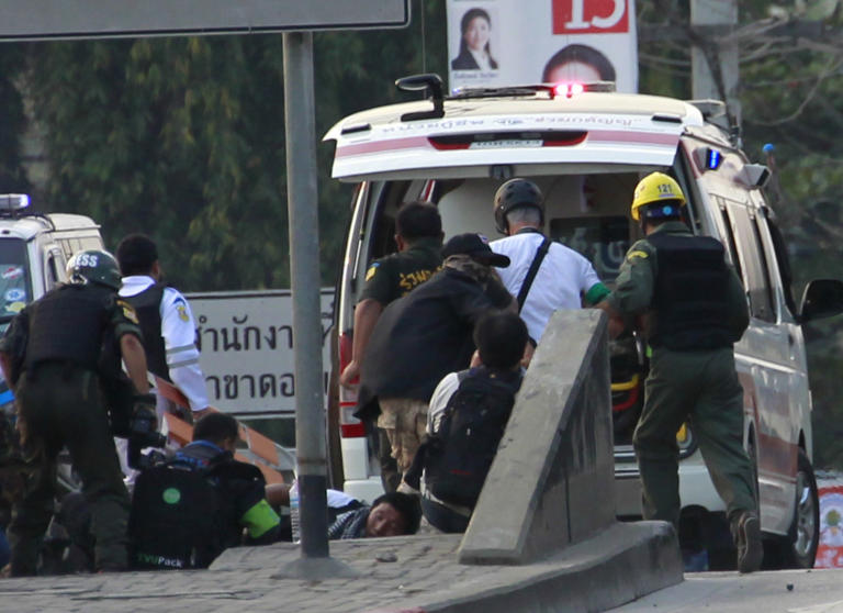 U.S. journalist James Nachtwey, second right in white shirt, is taken to an ambulance after he received a minor injury following clashes between anti and pro-government groups in Bangkok, Thailand Saturday, Feb. 1, 2014. Gunfire rang out at a major intersection in Thailand's capital on Saturday as clashes between protesters and government supporters erupted on the eve of tense nationwide elections. At least seven people were wounded, including an American photojournalist. (AP Photo/Wason Wanichakorn)