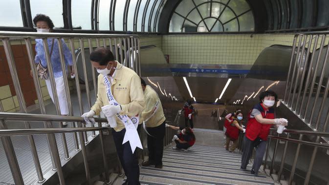 Pejabat pemerintah dan sukarelawan mendisinfeksi stasiun kereta bawah tanah di Goyang, Korea Selatan, Selasa (25/8/2020). Korea Selatan menutup sekolah dan beralih kembali ke pembelajaran jarak jauh setelah memasuki hari ke-12 peningkatan berturut-turut kasus COVID-19. (AP Photo/Ahn Young-joon)