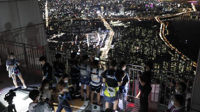 Orang-orang yang memakai masker wajah untuk membantu melindungi dari penyebaran virus korona, melihat pemandangan malam Seoul saat mereka menginap di tempat berkemah semalam di atap gedung pencakar langit di Seoul, Korea Selatan (7/8/2020). (AP Photo/Lee Jin-man)