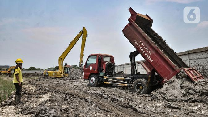 Petugas dari Dinas Bina Marga menggunakan kendaraan alat berat saat menyelesaikan penggarapan lahan untuk dijadikan lokasi pemakaman khusus Covid-19 di Rorotan, Jakarta, Selasa (29/9/2020). Lokasi ini sebelumnya merupakan kawasan pertanian. (merdeka.com/Iqbal S. Nugroho)