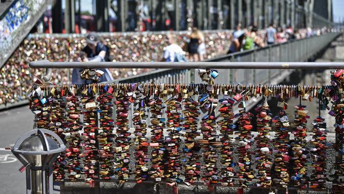 Kunci cinta Köln digantung di sebuah jembatan di Cologne, Jerman, Rabu, (5/8/2020). Sebagai bukti cinta mereka, puluhan ribu pasangan telah memasang gembok selama bertahun-tahun ke pagar di Jembatan Hohenzollern sebelum melemparkan kunci ke dalam Sungai Rhein di bawah. (AP Photo/ Martin Meissner)