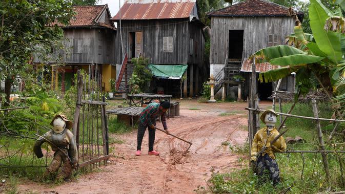 Dua orang-orangan sawah diikat ke pagar depan sebuah rumah di provinsi Kampong Cham, Kamboja, 11 Oktober 2020. Para petani di desa itu menggunakan orang-orangan sawah atau disebut juga Tim Mong untuk menangkal virus corona Covid-19 berdasarkan kepercayaan yang mereka yakini. (TANG CHHIN Sothy/AFP)