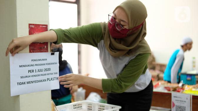 Petugas menempel pengumuman terkait penggunaan kantong plastik di Pasar Mitra Tani, Jakarta, Selasa (30/6/2020). Pasar Mitra Tani akan melarang penggunaan kantong plastik sekali pakai untuk seluruh vendor dan konsumen pasar mulai Rabu, 1 Juli 2020. (Liputan6.com/Angga Yuniar)