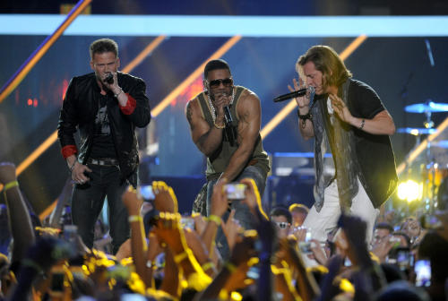 Brian Kelley, left, and Tyler Hubbard, right, of musical group Florida Georgia Line, and Nelly perform at the 2013 CMT Music Awards at Bridgestone Arena on Wednesday, June 5, 2013, in Nashville, Tenn. (Photo by Donn Jones/Invision/AP)