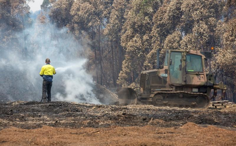 An Australian Army combat engineer from the 5th Engineer Regiment utilises a JD-450 Bulldozer to spread out burnt woodchip at the Eden Woodchip Mill in southern New South Wales
