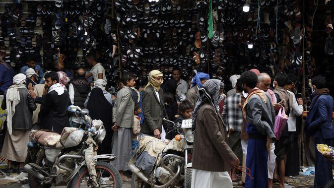 Warga berbelanja sepatu di sebuah pasar menjelang Hari Raya Idul Fitri di Sanaa, Yaman, Jumat (22/5/2020). Idul Fitri menandai berakhirnya bulan suci Ramadan. (Xinhua/Mohammed Mohammed)