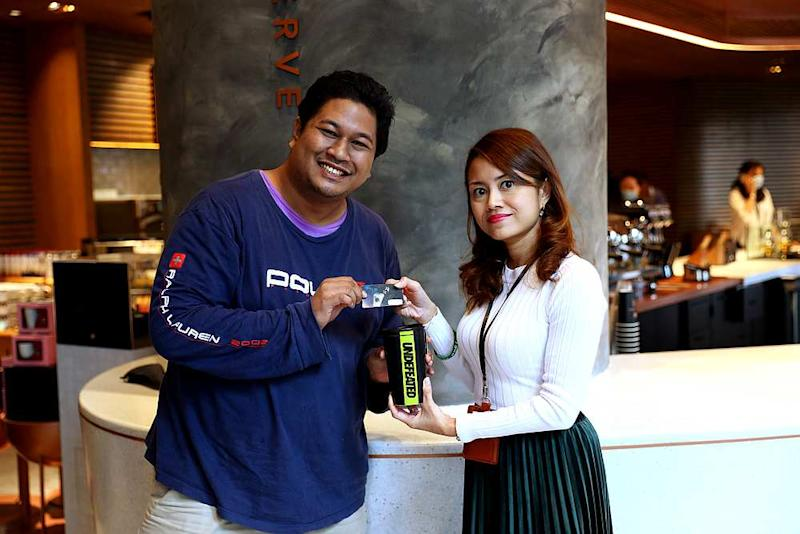 Marketing and loyalty senior manager Thila Chandran (right) presenting Luqman with the Starbucks and Undefeated merchandise and a Starbucks Rewards card. — Picture courtesy of Starbucks Malaysia