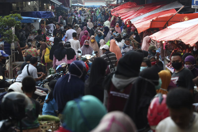 People shop in preparation of the upcoming Eid al-Fitr holiday that marks the end of the holy fasting month of Ramadan amid fears of the new coronavirus outbreak at a market in Jakarta, Indonesia, Friday, May 22, 2020. (AP Photo/Achmad Ibrahim)