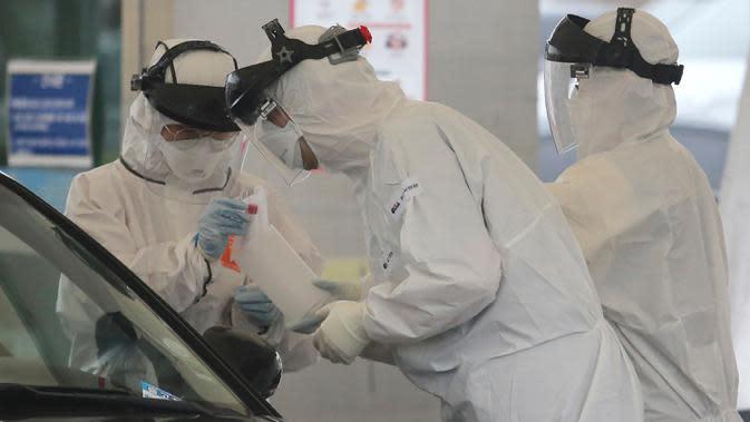 Petugas medis dengan pakaian pelindung mengambil sampel dari pengemudi di layanan