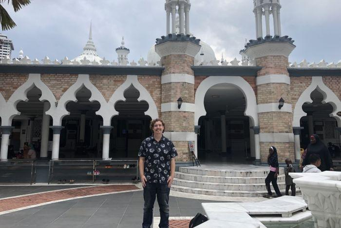 Man standing in front of a mosque