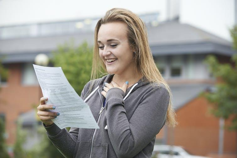 Happy girl looking at results paper