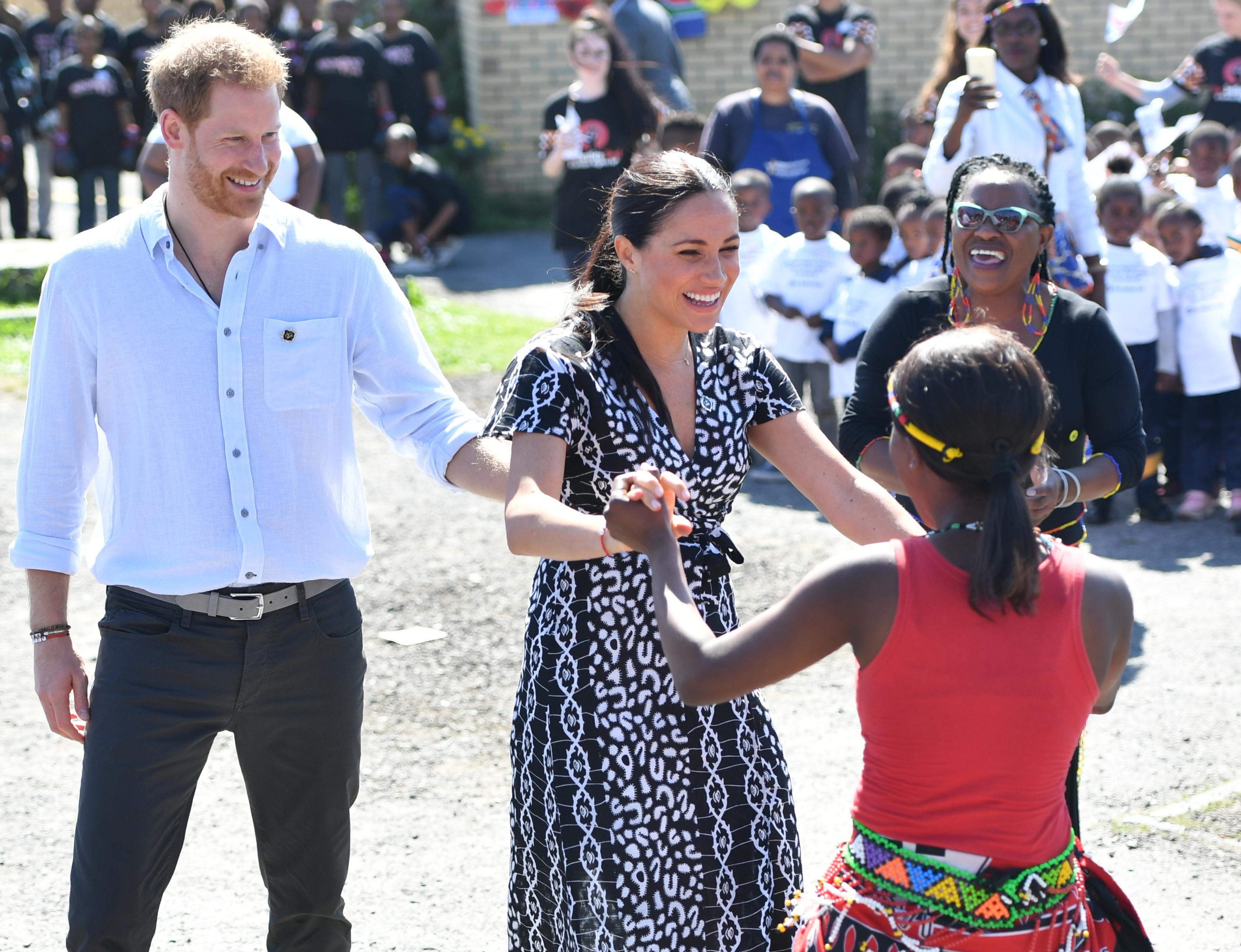 Meghan dances with a local during the engagement at the Nyanga township in Cape Town. [Photo: Getty]