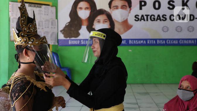 Penari tradisional dari Sanggar Eschoda menggunakan masker dan pelindung wajah sebelum berlatih di Kota Tangerang, Jumat (12/6/2020). Para penari itu menerapkan protokol kesehatan jelang new normal atau tatanan hidup normal, sekaligus sebagai upaya pencegahan Covid-19. (Liputan6.com/Angga Yuniar)