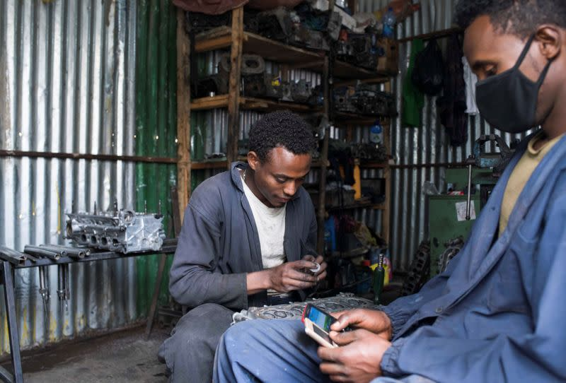 A mechanic works inside his opened garage store after protests which disrupted business, in Addis Ababa