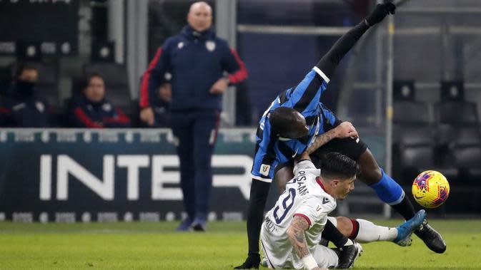 Pemain Inter Milan Romelu Lukaku (atas) duel bola dengan pemain Cagliari Fabio Pisacane pada pertandingan Coppa Italia di Stadion San Siro, Milan, Italia, Selasa (14/1/2020). Inter Milan menang 4-1 dengan dua gol disumbang Lukaku. (AP Photo/Antonio Calanni)