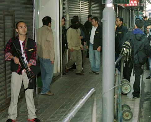 Police escort Kwai Ping-hung out of a building in Yau Ma Tei in 2003. Photo: Handout