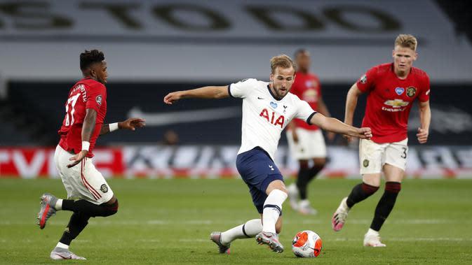 Striker Tottenham Hotspur, Harry Kane, berusaha melewati pemain Manchester United dalam laga lanjutan Premier League 2019/20 di Tottenham Hotspur Stadium, Sabtu (20/6/2020) dini hari WIB. Manchester United bermain imbang 1-1 atas Tottenham. (AFP/Matthew Childs)