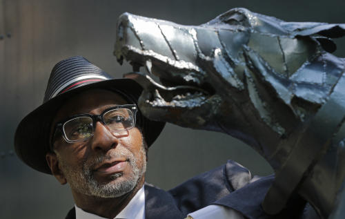 "Rev. Isreal Grant looks at a statue of attacking dogs at Kelly Ingram Park in Birmingham, Ala., Friday, Sept. 6, 2013. When he was 15, Grant boarded an overcrowded bus and, finding no place at the back, sat down beside an elderly white woman. He was arrested and jailed overnight, without even being given a chance to call his parents. ""My father found me the next morning,"" Grant recalls. ""They had been checking all the funeral homes and all the police stations. My father cried like a baby."" Because of his good grades and lack of a record, the judge agreed to dismiss the charges. (AP Photo/Dave Martin)"