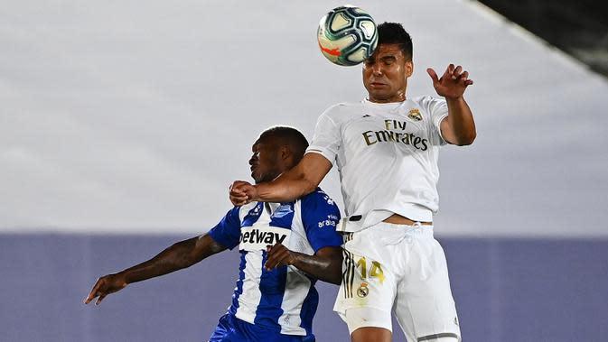 Gelandang Real Madrid, Casemiro melompat saat berebut bola dengan pemain tengah Alaves, Jose Luis Rodriguez pada lanjutan Liga Spanyol di stadion Alfredo di Stefano, Sabtu (11/7/2020). Real Madrid menang 2-0 lewat gol Karim Benzema dan Marco Asensio. (GABRIEL BOUYS/AFP)