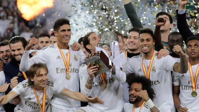 Pemain Real Madrid Sergio Ramos (tengah) mencium trofi juara Piala Super Spanyol bersama rekan-reakannya usai mengalahkan Atletico Madrid pada pertandingan final di King Abdullah Stadium, Jeddah, Arab Saudi, Senin (13/1/2020). Real Madrid menang adu penalti 4-1. (AP Photo/Hassan Ammar)