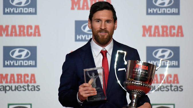 Penyerang Barcelona, Lionel Messi berpose setelah menerima penghargaan Pichichi Trophy untuk pencetak gol terbanyak 2016-17 di liga Spanyol dan Alfredo Di Stefano Trophy di Barcelona (18/12). (AFP Photo/Lluis Gene)