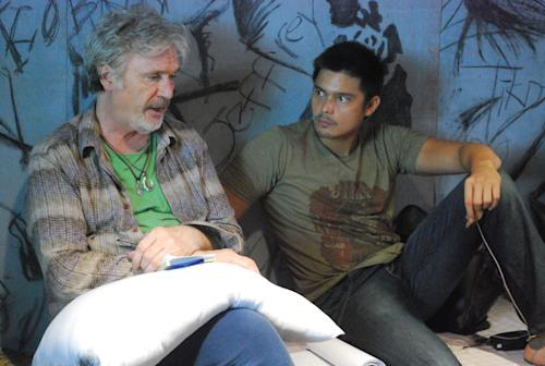 """In this handout photo taken March, 2010 and released by Portfolio Films Wednesday, April 3, 2013, Irish actor Patrick Bergin, left, talks with Filipino heartthrob Dingdong Dantes during a scene at the Cebu Provincial Detention and Rehabilitation Center in Cebu province, central Philippines. The Filipino inmates whose choreographed """"Thriller"""" dance has attracted 52 million YouTube hits since 2007 are getting their own stories told in a movie """"Dance of the Steel Bars"""". (AP Photo/Portfolio Films) NO SALES"""