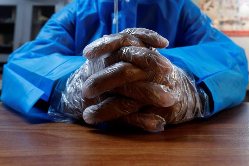 A volunteer of the Edhi Foundation, a non-profit social welfare programme, wears disposable polythene gloves during an awareness session on handling suspected carriers of coronavirus disease (COVID-19), in Karachi, Pakistan