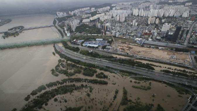 Sebagian jalan utama dan taman di dekat Sungai Han terendam banjir akibat hujan lebat di Seoul, Korea Selatan, Kamis (6/8/2020). Hujan lebat terus mengguyur Korea Selatan, mendorong pihak berwenang untuk menutup sebagian jalan raya dan mengeluarkan peringatan banjir. (AP Photo/Lee Jin-man)