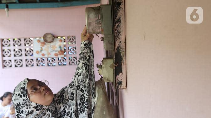 Warga memeriksa meteran listrik di kawasan Matraman, Jakarta, Kamis (2/4/2020). Pemerintah menggratiskan biaya tarif listrik bagi konsumen 450 Volt Ampere (VA) dan pemberian keringanan tagihan 50 persen kepada konsumen bersubsidi 900 VA mulai April hingga Juli 2020. (Liputan6.com/Herman Zakharia)