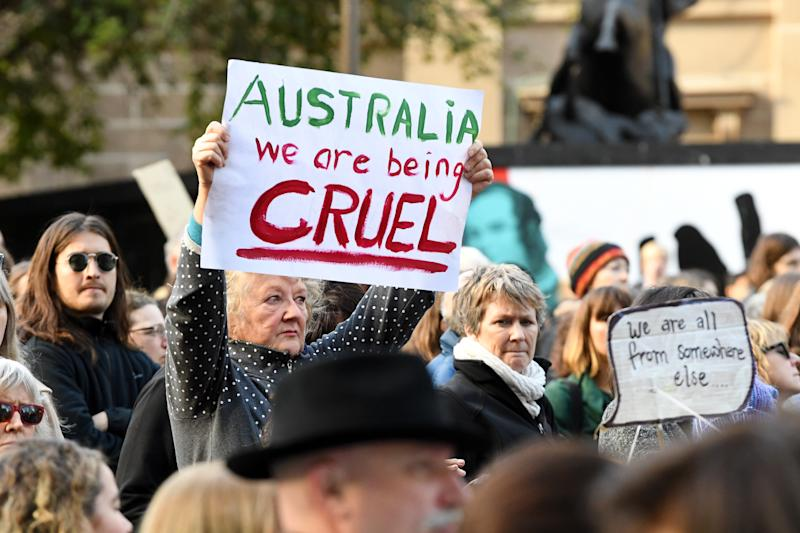 Protesters are seen outside of the State Library of Victoria in Melbourne. Rallies have taken place in Canberra, Sydney, Melbourne, Brisbane marking six years since offshore detention on Manus and Nauru was implemented.