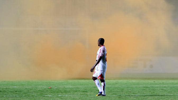 Pemain Persipura Yustinus Pae berjalan melihat ke arah asap flare saat melawan Arema Cronus pada laga Piala Jenderal Sudirman 2015 di Stadion Maguwoharjo, Sleman, Minggu (13/12/2015). (Bola.com/Nicklas Hanoatubun)