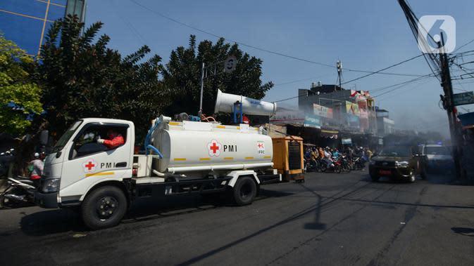 Petugas gabungan melakukan penyemprotan cairan disinfektan di sepanjang jalan raya di wilayah Jakarta Timur, Selasa (25/8/2020). Hal ini mengingat jumlah kasus positif Covid-19 yang meningkat di wilayah Jakarta Timur agar masyarakat tetap sehat dan saling menjaga protokol kesehatan. (merdeka.com/Ima