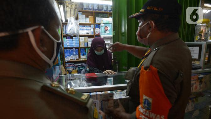 Petugas gabungan melakukan razia pertokoan dan tempat makan di Pasar Pramuka, Jakarta, Kamis (24/9/2020). Upaya mencegah penularan virus corona terus dilakukan dengan merazia pertokoan dan warung makan yang masih melayani makan di tempat. (merdeka.com/Imam Buhori)