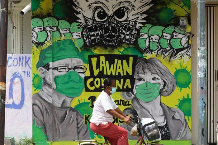 A woman rides her bicycle past a coronavirus awareness mural depicting medical workers in Indonesia.