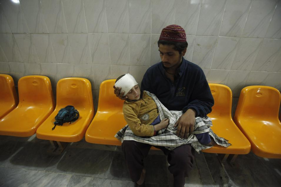 A man carries his brother, injured in a grenade attack, as he waits for treatment at the Lady Reading Hospital in Peshawar